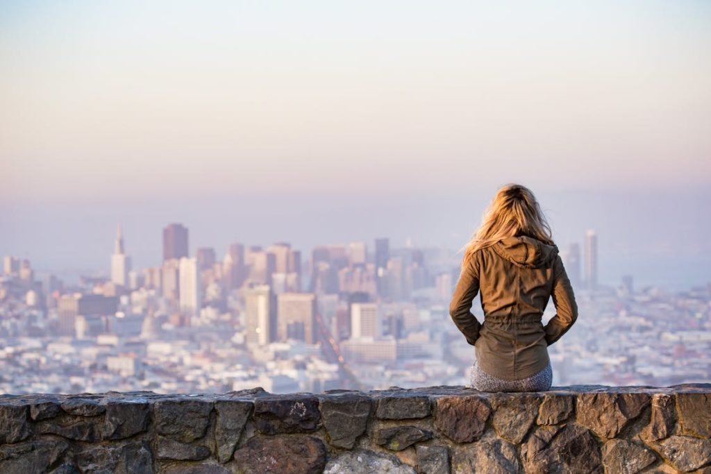 woman pondering back city